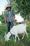 Ein älterer Mann mit einer weißen Ziege lizenzfreie stockfotografie
