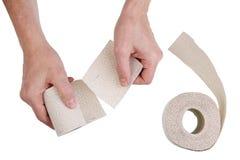 Ein älterer Mann mit seinen Händen reißt ein Stück Toilettenpapier auseinander lizenzfreie stockbilder
