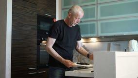 Ein älterer Mann nimmt an der Zubereitung des Lebensmittels in der Küche ihres eigenen apartomentov teil stock video