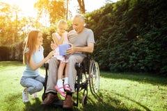 Ein älterer Mann sitzt in einem Rollstuhl Er wird von einer Frau mit einem Mädchen gesehen Das Mädchen sitzt auf dem Mann ` s Sch lizenzfreie stockfotos