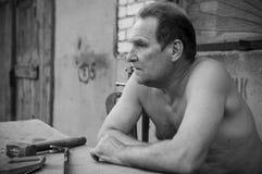 Ein älterer Mann sitzt an einem Tisch mit einem Bauschlosserwerkzeug Stockbild