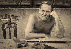 Ein älterer Mann sitzt an einem Tisch mit einem Bauschlosserwerkzeug Lizenzfreie Stockfotografie
