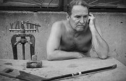 Ein älterer Mann sitzt an einem Tisch mit einem Bauschlosserwerkzeug Lizenzfreies Stockbild