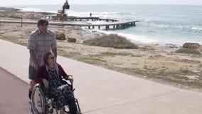 Ein älterer Mann trägt eine Frau in einem Rollstuhl entlang der Promenade stock video footage