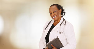 Ein älterer schwarzer Doktor, der für ein Porträt in ihrem Büro aufwirft Lizenzfreie Stockbilder