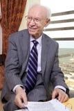 Älterer Geschäftsmann, der weg lächelt Lizenzfreies Stockfoto