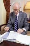 Älterer Geschäftsmann, der über Papiere hinausgeht Lizenzfreie Stockfotografie