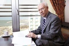 Älterer Geschäftsmann, der über Papiere hinausgeht Stockbilder