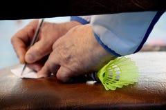 ein älterer Trainer nimmt Kenntnisse mit einem Federball für Badminton in seiner Faust und gestaltet Nahaufnahme stockbild