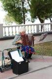Ein älterer trauriger männlicher Musiker spielt für Passanten auf der Seeseite stockbilder