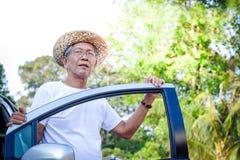 Ein älteres asiatisches Mannautofahren lizenzfreies stockfoto