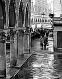Ein älteres Paar, das auf die nass Straßen von Venedig nahe Rialto-Brücke und die Säulengänge des Fischmarktes geht Italien stockbilder