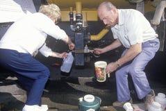 Ein älteres Paar, das etwas Wasser von einem Wasser sichert lizenzfreie stockfotografie