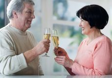 Ein älteres Paar, das ihre Jahre zusammen mit champag röstet Stockfoto