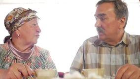 Ein älteres Paar trinkt Tee von einem russischen Kesselsamowar der Weinlese Ein Mann mit einem Schnurrbart sprechend mit seiner F stock footage