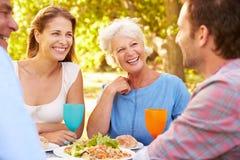 Ein älteres und junges erwachsenes Paar, das zusammen draußen isst Stockbilder