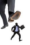 Ein ängstlicheinbrecher, der weg von einem großen Fuß läuft Lizenzfreies Stockbild