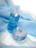 Ein öffnete Flasche Duftstoff auf einem blauen Hintergrund mit Kerze Lizenzfreies Stockfoto