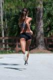 Ein übender Wind der Frau sprintet auf der Straße Stockfotos