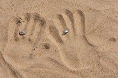 Ein Abdruck der Hände im Sand mit Ringen. Stockfotografie