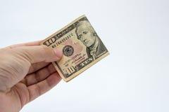 Ein Abschluss herauf Bild einer kaukasischen männlichen Hand, die eine zehn-Dollar-Anmerkung mit einem einfachen Hintergrund hält Stockbilder