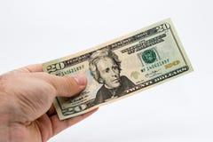 Ein Abschluss herauf Bild einer kaukasischen männlichen Hand, die eine zehn-Dollar-Anmerkung mit einem einfachen Hintergrund hält Stockfotos