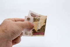 Ein Abschluss herauf Foto einer kaukasischen männlichen Hand, die eine Anmerkung des russischen Rubels 100 hält Stockbild