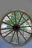 Ein Abschluss oben eines ungewöhnlichen Fensters gemacht von einem alten Wagenrad lizenzfreie stockfotografie