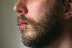 Ein Abschluss oben von a bemannt Gesicht mit einem Durchdringen Stockbild