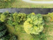 Ein Abzugsgraben füllte mit Wasser auf einer Wiese mit einem Baum, Zusammenfassung als b Stockbild