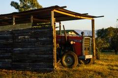 Ein Ackerschlepper, der unter Abdeckung im frühen Sonnenschein sitzt Lizenzfreie Stockbilder