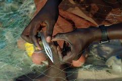 Ein afrikanischer Fischer, der sein Netz repariert Stockfotografie