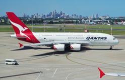 Ein Airbus A380 von Qantas mit den Sydney-Skylinen Stockbild
