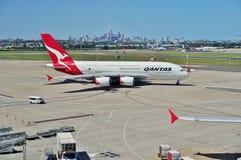 Ein Airbus A380 von Qantas mit den Sydney-Skylinen Lizenzfreie Stockbilder