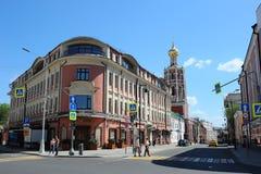 Ein Altbau auf Petrovka-Straße und der Glockenturm des hoch--Petrovsky Klosters, Moskau, Russland Lizenzfreie Stockfotos