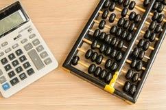 Ein alter chinesischer Abakus und ein moderner Taschenrechner Lizenzfreies Stockfoto