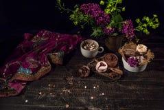 Ein alter flüssiger purpurroter transparenter Schal in der orientalischen Art auf einem Holztisch mit Kaffee Stockfotografie