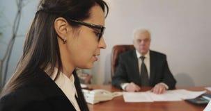 Ein alter grauhaariger Geschäftsmann lud Brunettefrau zu seinem Büro für eine Sitzung ein stock video