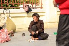 Ein alter heimatloser Mann zählen ihn Geld Lizenzfreie Stockbilder