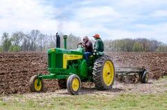 Ein alter John Deere-Traktor in einem pflügenden Ereignis Lizenzfreie Stockfotos