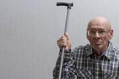 Ein alter kahler Mann mit Gl?sern bewegt einen Spazierstock wellenartig stockfotografie