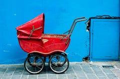Ein alter Kinderwagen gegen eine blaue Wand Lizenzfreies Stockbild