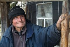 Ein alter Mann in den nachl?ssigen Kleidungsst?nden an der Schwelle zu seinem eigenen ruinierten Haus und in den Blicken in den A stockfotografie