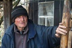 Ein alter Mann in den nachl?ssigen Kleidungsst?nden an der Schwelle zu seinem eigenen ruinierten Haus und in den Blicken in den A stockbild
