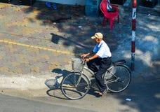 Ein alter Mann, der auf Straße in Saigon radfährt lizenzfreie stockfotografie