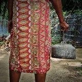 Ein alter Mann, der den colurful Batik trägt ein rostiges keetle trägt Stockfotos