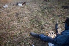 Ein alter Mann in der unordentlichen Kleidung sitzt auf einem Hügel, der das Schach spielt und lässt eine Menge seiner eigenen Zi stockfotografie
