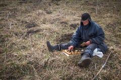 Ein alter Mann in der unordentlichen Kleidung und in einer Kappe sitzt auf einem Hügel, der im Frühjahr Schach gegen den Hintergr stockfotos