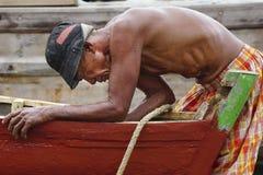 Ein alter Mann hält ein defektes Boot instand lizenzfreie stockbilder