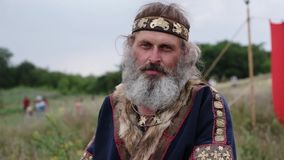 Ein alter Mann im ethnischen Kostüm mit großem weißem Bart steht und schaut traurig und auf einem Gebiet müde stock footage
